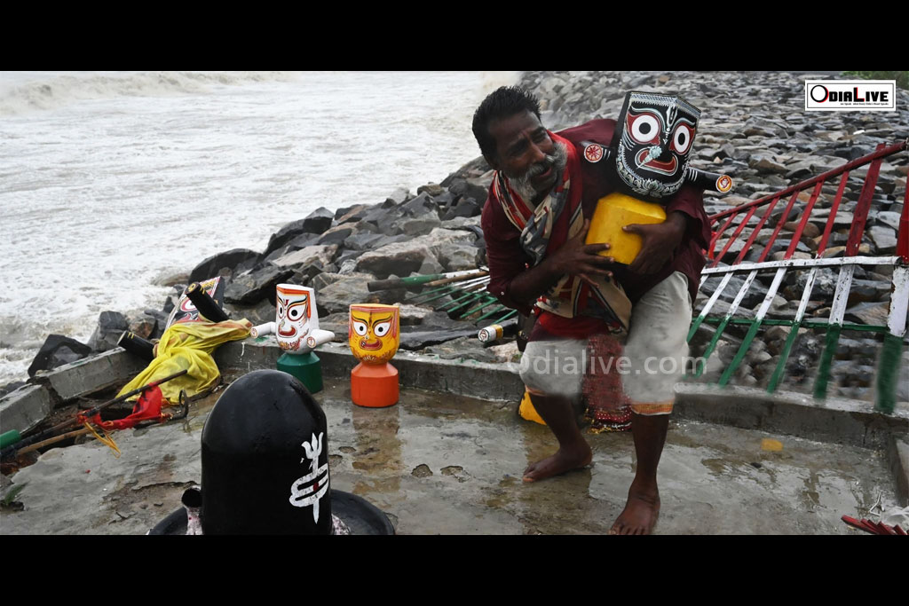 The priest with Lord Jagannath idol during Cyclone Yaas
